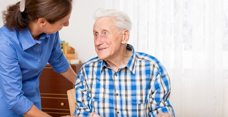 An elderly gentleman talks with a member of the care team