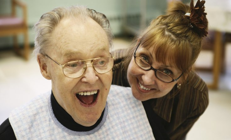 A manager in a nursing home enjoys sharing a joke with a service user