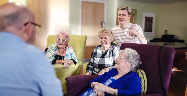 A home manager in a care home talks to residents